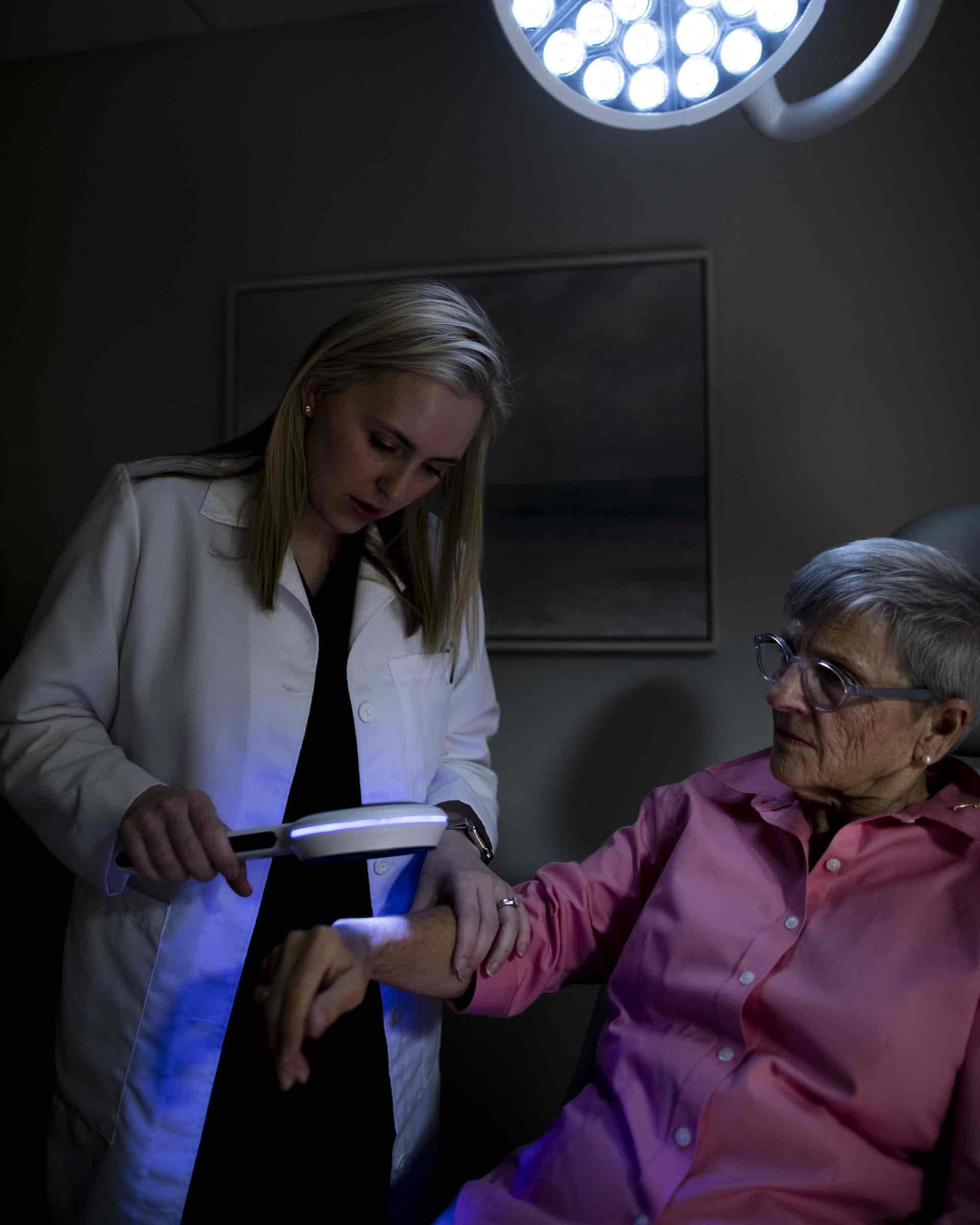 A doctor is holding an elderly woman's arm beneath a ray of light in order to find the problem area.